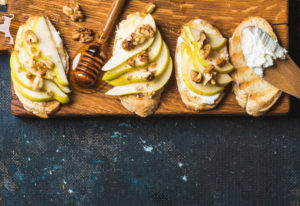 Crostini with pear, ricotta cheese, honey and walnuts. Breakfast toasts or snack sandwiches on rustic wooden board over dark blue grunge plywood background. Top view, copy space